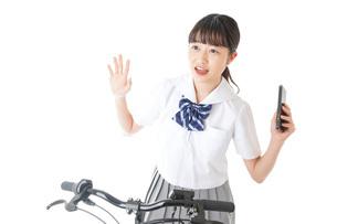 自転車でスマホを使う若い学生の写真素材 [FYI04716026]