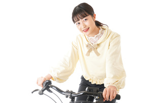 自転車を運転する若い女性の写真素材 [FYI04716030]