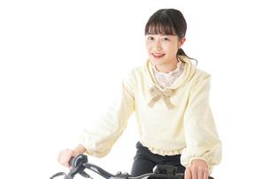 自転車に乗る若い女性の写真素材 [FYI04716034]