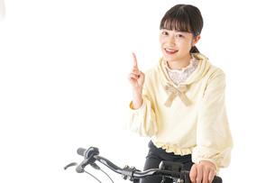 自転車を運転する若い女性の写真素材 [FYI04716037]