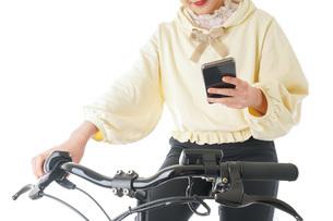 自転車でスマホを使う若い女性の写真素材 [FYI04716064]