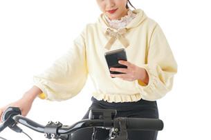 自転車でスマホを使う若い女性の写真素材 [FYI04716067]