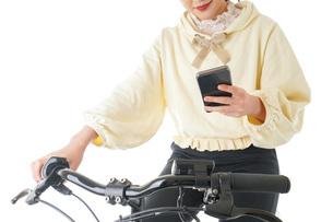 自転車でスマホを使う若い女性の写真素材 [FYI04716068]