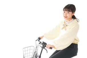 自転車を運転する若い女性の写真素材 [FYI04716077]