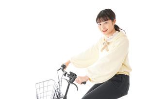 自転車を運転する若い女性の写真素材 [FYI04716078]
