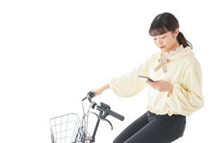 自転車でスマホを使う若い女性の写真素材 [FYI04716098]