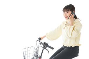 自転車でスマホを使う若い女性の写真素材 [FYI04716103]