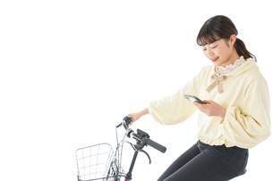 自転車でスマホを使う若い女性の写真素材 [FYI04716105]