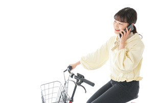 自転車でスマホを使う若い女性の写真素材 [FYI04716106]