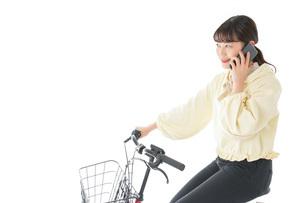 自転車でスマホを使う若い女性の写真素材 [FYI04716107]