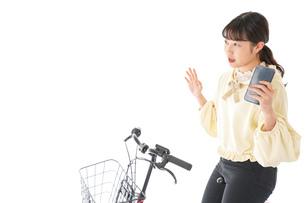 自転車を運転する若い女性の写真素材 [FYI04716112]