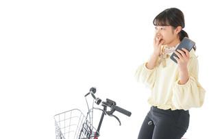 自転車でスマホを使う若い女性の写真素材 [FYI04716117]