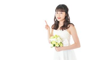 ブーケを持ち指差す花嫁の女性の写真素材 [FYI04716266]