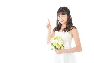 ブーケを持ち指差す花嫁の女性の写真素材 [FYI04716267]