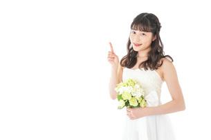 ブーケを持ち指差す花嫁の女性の写真素材 [FYI04716269]