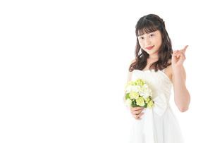 ブーケを持ち指差す花嫁の女性の写真素材 [FYI04716276]