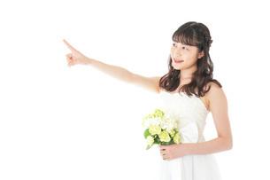 ブーケを持ち指差す花嫁の女性の写真素材 [FYI04716294]