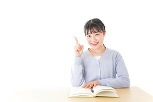 勉強をしながら指を指す若い女子学生の写真素材 [FYI04716535]