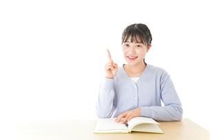 勉強をしながら指を指す若い女子学生の写真素材 [FYI04716547]