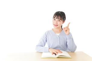 勉強をしながら指を指す若い女子学生の写真素材 [FYI04716548]