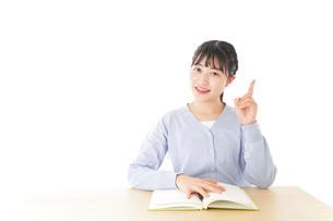 勉強をしながら指を指す若い女子学生の写真素材 [FYI04716551]
