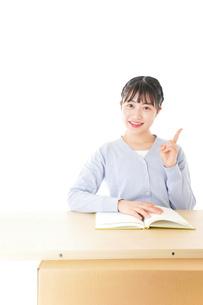勉強をしながら指を指す若い女子学生の写真素材 [FYI04716553]