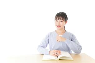 勉強をしながら指を指す若い女子学生の写真素材 [FYI04716565]