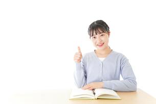 勉強をしながら指を指す若い女子学生の写真素材 [FYI04716566]