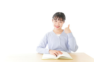 勉強をしながら指を指す若い女子学生の写真素材 [FYI04716567]