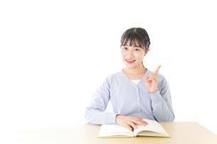 勉強をしながら指を指す若い女子学生の写真素材 [FYI04716576]