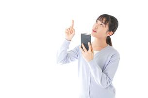 IOT家電をスマホで操作する若い女性の写真素材 [FYI04716622]