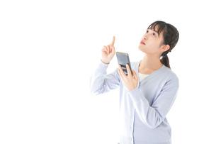 IOT家電をスマホで操作する若い女性の写真素材 [FYI04716623]