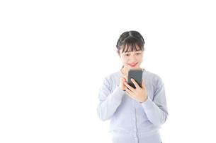 スマホを使う若い女子学生の写真素材 [FYI04716627]