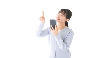IOT家電をスマホで操作する若い女性の写真素材 [FYI04716631]