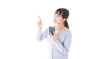 IOT家電をスマホで操作する若い女性の写真素材 [FYI04716632]