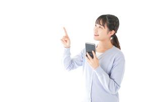 IOT家電をスマホで操作する若い女性の写真素材 [FYI04716633]