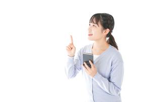 IOT家電をスマホで操作する若い女性の写真素材 [FYI04716636]