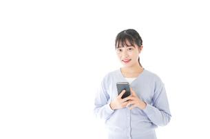スマホを使う若い女子学生の写真素材 [FYI04716637]