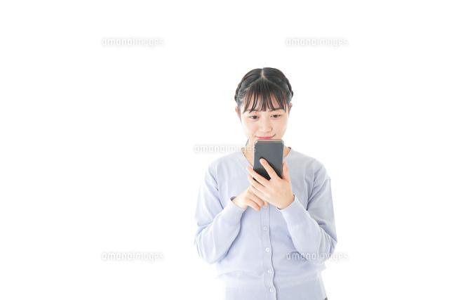 スマホを使う若い女子学生の写真素材 [FYI04716641]