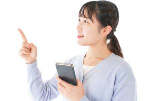 IOT家電をスマホで操作する若い女性の写真素材 [FYI04716642]