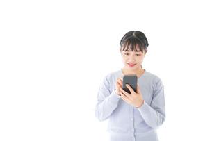 スマホを使う若い女子学生の写真素材 [FYI04716643]