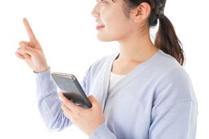 IOT家電をスマホで操作する若い女性の写真素材 [FYI04716644]