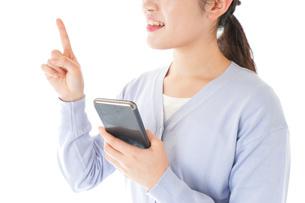 IOT家電をスマホで操作する若い女性の写真素材 [FYI04716645]
