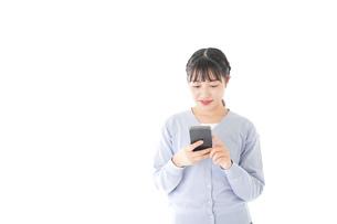 スマホを使う若い女子学生の写真素材 [FYI04716646]