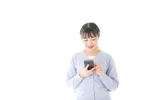 スマホを使う若い女子学生の写真素材 [FYI04716647]