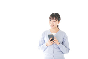 スマホを使う若い女子学生の写真素材 [FYI04716648]