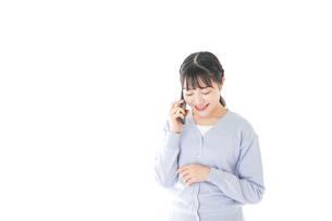 スマホを使う若い女子学生の写真素材 [FYI04716650]