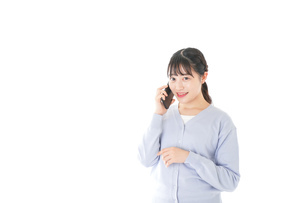 スマホを使う若い女子学生の写真素材 [FYI04716651]