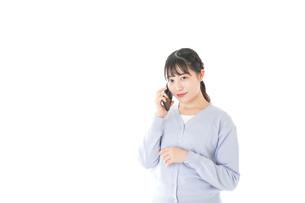 スマホを使う若い女子学生の写真素材 [FYI04716656]