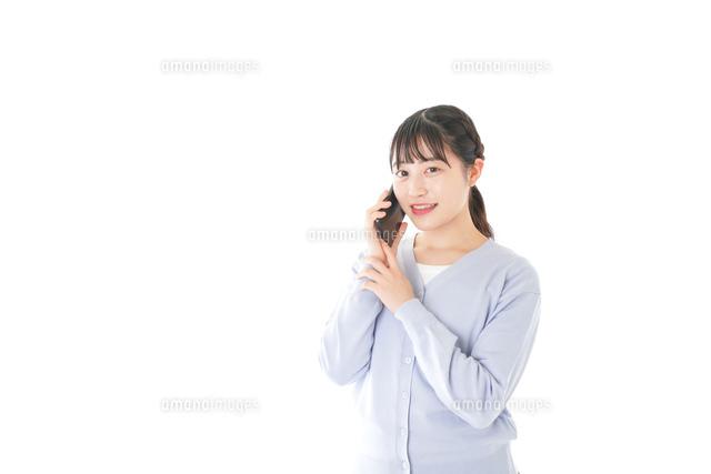 スマホを使う若い女子学生の写真素材 [FYI04716657]